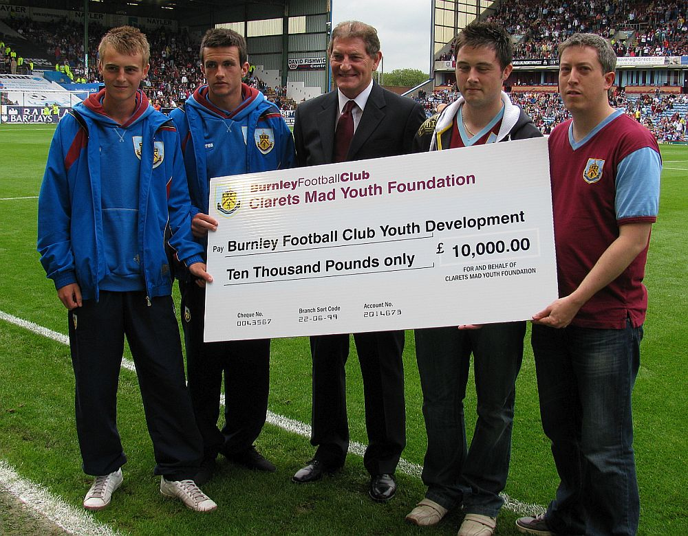 Martin Dobson receives a cheque for £10,000 to allow the youth team to take part in the Northern Ireland Milk Cup