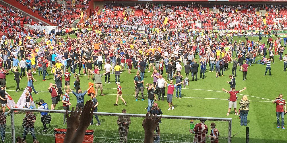 Burnley fans flood the pitch at Charlton after the title is won
