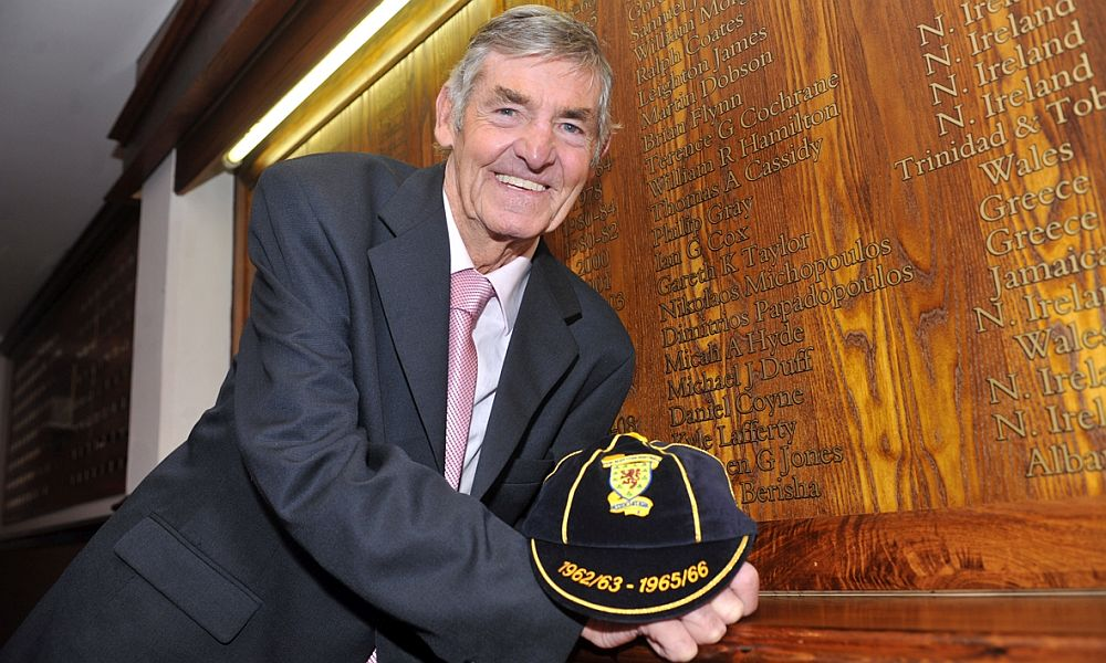 Adam with his cap in front of the international honours board at Turf Moor