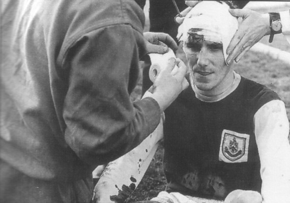 Les Latcham receives treatment from George Bray after a clash of heads with Altafini
